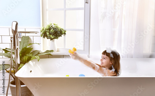 Photo Happy little baby girl sitting in bath tub  in the bathroom