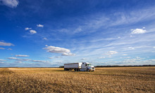 Heavy Transport Truck And Trailer Parked In A Golden Harvested Field Under A Cloudy And Sunny Countryside Autumn Landscape