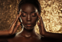 Fashion Studio Portrait Of An Extraordinary Beautiful African American Model With Closed Eyes  Over Golden Background