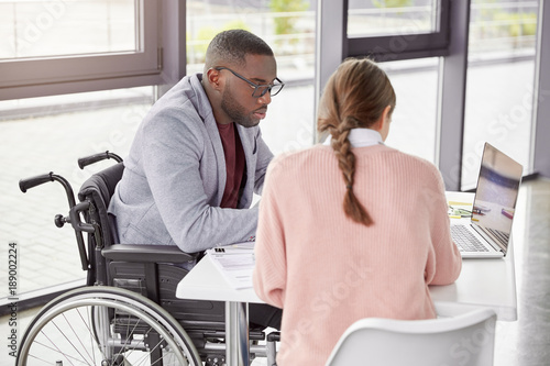 Photo  Serious dark skinned male invalid in wheelchair collaborates with young female, make business plan together, watch online conference or webinar online, sit in spacious cabinet