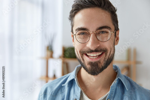 Tablou Canvas Close up shot of cheerful satisfied attractive male with stubble, has broad smile, wears round spectacles, rejoices success at work, stands against cozy interior