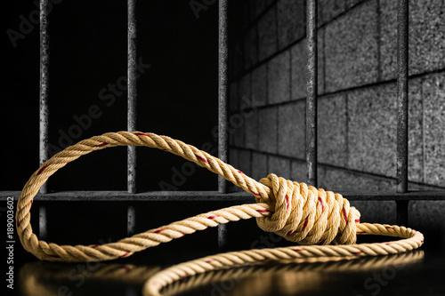 Obraz na plátně  Brown rope noose dark and light on black table with old prison bars cell lock ba
