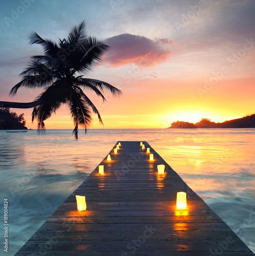 Foto op Plexiglas Oceanië romantic beach with wooden jetty and lamps, romantic travel