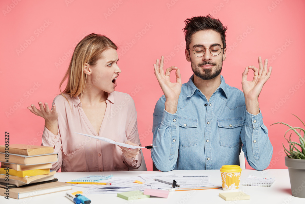 Fototapeta Angry irritated pretty female student looks at male partner who meditates at working table, tries to relax for continuing hard work on course paper, isolated over pink background. Exam preparation