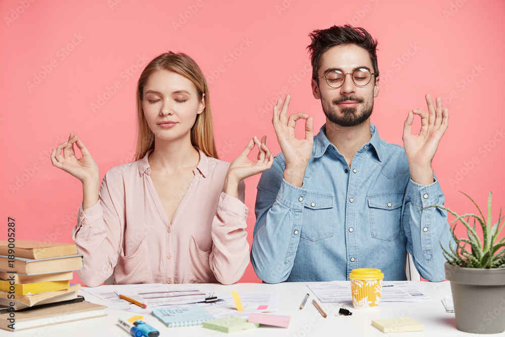 Fototapeta Isolated shot of two female and male coworkers, meditate and keeps eyes shut, try to relax after exam preparation, cramm material from many books, sit at working desk against pink background