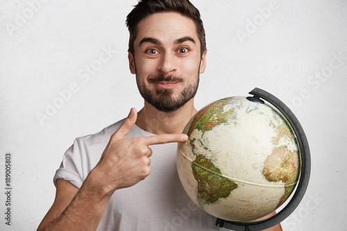 Fotografie, Tablou  Positive brunet male traveller chooses place to go on earth, holds world globe, isolated over white background