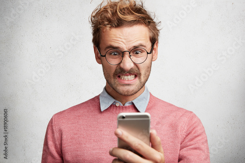 Fotografía  Angry irritated male reads text message on smart phone remind him about bills, n