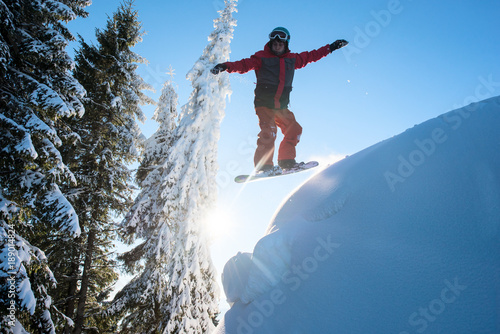 Tuinposter Wintersporten Freerider snowboarder jumping in the air while riding on the slope in the mountains. Blue sky and sun on the background. Ski season and winter sports concept