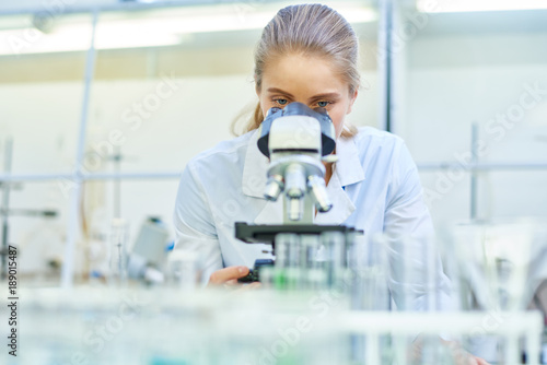 Portrait of young female scientist looking in microscope while working on medical research in science laboratory, copy space