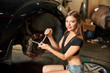Close-up of beautiful girl is sitting on a tire near a black car repairing the front wheel in the garage. A girl looks at the camera with a smile