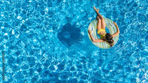 Obraz na płótnie Widok z lotu ptaka z góry dziewczyna w basenie z góry, dziecko pływa na nadmuchiwane pierścień cukierka, dziecko ma zabawy w wodzie na rodzinne wakacje