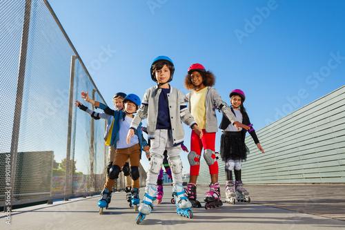 Preteen kids rollerblading outdoors at stadium