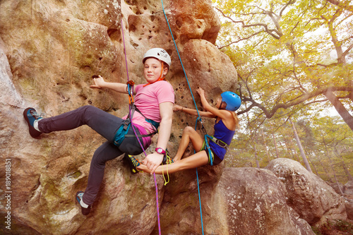 Young girl climbs a rock with female instructor