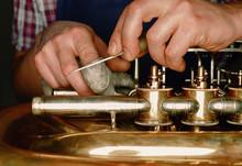 A Craftsmen Adjusts A Brass In...
