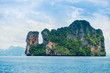 a picturesque island - a rock covered with greenery in a sea horizontal landscape