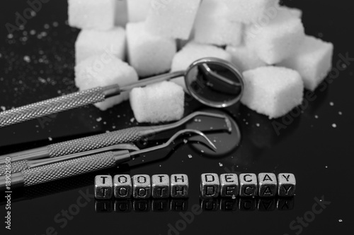 Dentist tools and mirror with sugar cubes and the words tooth decay on beads Wallpaper Mural