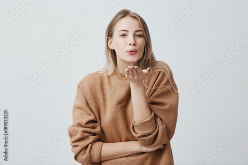 Fotografía  Attractive dreamy female model with blonde hair pouts lips, sends kisses to camera, poses against gray background