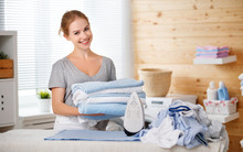 Happy Woman Housewife Ironing Clothes   In Laundry At Home