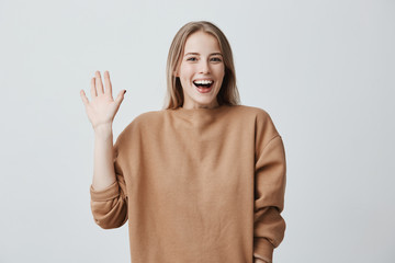 Friendly positive blonde female smiling broadly and happily camera, dressed in loose sweater, greeting her friends, pleased to meet them. Positive emotions, feelings and face expression.