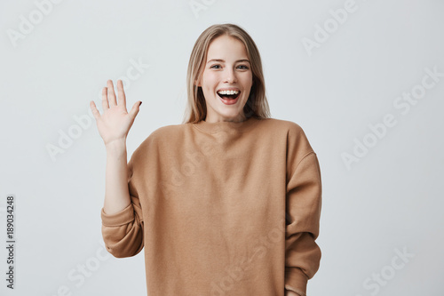 Obraz Friendly positive blonde female smiling broadly and happily camera, dressed in loose sweater, greeting her friends, pleased to meet them. Positive emotions, feelings and face expression. - fototapety do salonu