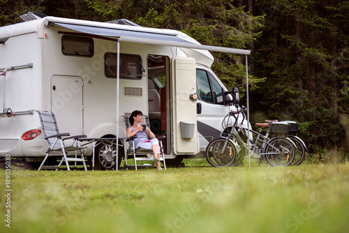 Woman is standing with a mug of coffee near the camper RV.