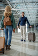 Content adult male and female travelers meeting up in the terminal. Everyone carrying own luggage