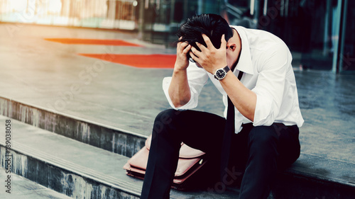 Fotografia  Unemployed Tired or stressed businessman sitting on the walkway after work Stres