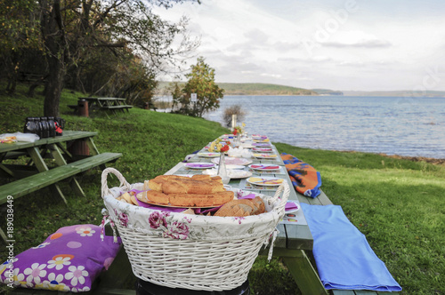Foto op Aluminium Picknick A fancy picnic table full of food by lake in spring
