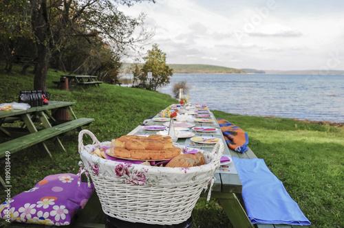 Keuken foto achterwand Picknick A fancy picnic table full of food by lake in spring