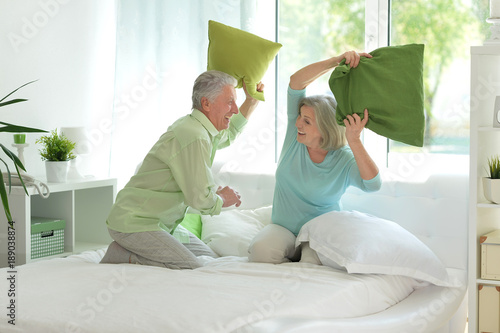 couple  fighting with pillows  in bed Poster