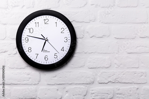 Wall clock on white brick wall