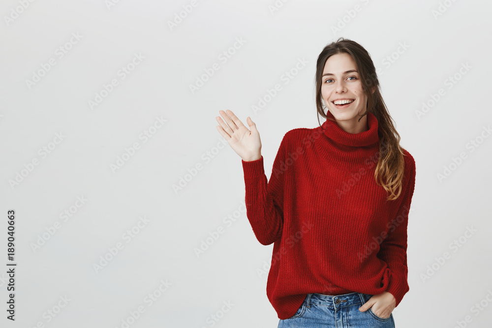 Fototapety, obrazy: Young attractive student with beautiful long brown hair smiling broadly, waving showing hello gesture over white background. Pleasant attractive girl came to her work, greeting coworkers cheerfully.