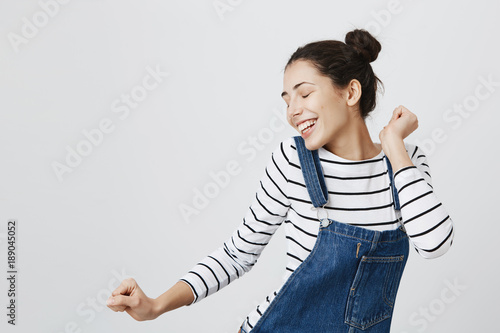 Valokuva  Portrait of brunette Caucasian hipster girl dancing against gray blank wall with smile, rejoicing good mood