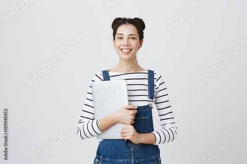 Valokuva  Positive caucasian female student in denim overall with two hairbuns smiling broadly with teeth at camera, having good mood, holding laptop computer in hands