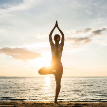 Silhouette Of A Woman Practicing The Tree Yoga Pose On A Beach At Sunset During Summer Vacation