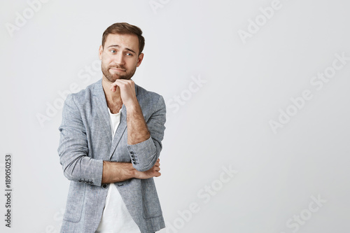 Fotografía  Headshot of serious bearded male has attentive look, keeps hand under chin, poses against gray studio wall, listens news