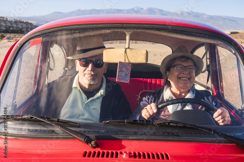 Fotografía  elderly couple with hats inside old red car