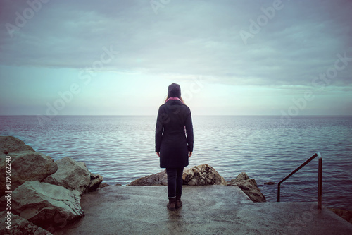 Fotomural back view of lonely woman looking the see, loneliness concept in winter season