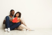 Happy African-american Couple In Love Holding Red Paper Heart