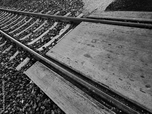 Valokuva  Railroad tracks and crossing in black and white.