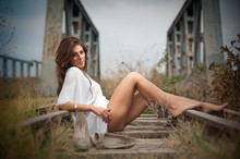 Attractive Woman With Short White Dress And Long Hair Provocatively Stretched Out On The Railroad With Bridge In Background.  Girl With Sexy Body And Long Legs On The Bridge Posing In  White Dress