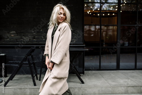 Stampa su Tela Portrait of beautiful young stylish blonde woman wearing beige coat and walking through the city streets