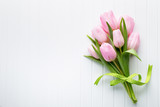 Fototapeta Tulipany - Fresh red tulip flowers bouquet on shelf in front of wooden wall.