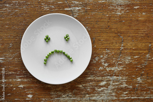 Valokuvatapetti sad hungry smiley face out of peas on plate