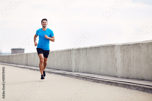 Foto  Handsome man running outdoors
