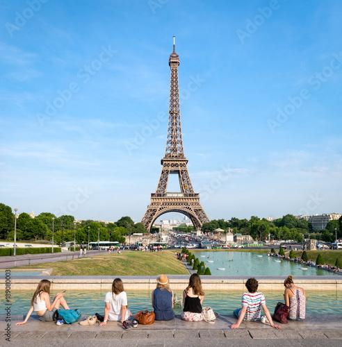 Grupa turystów relaksuje się przed Wieżą Eiffla w Paryżu, Francja