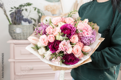 beautiful luxury bouquet of mixed flowers in woman hand. the work of the florist at a flower shop. cute lovely girl © malkovkosta