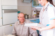 The young doctor standing near ill old man and holding photo album in hands at home