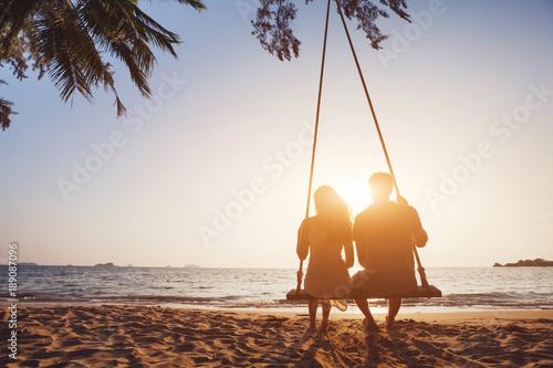 Fotografia  Romantyczna para zakochanych siedzi razem na huśtawce liny o zachodzie słońca pl