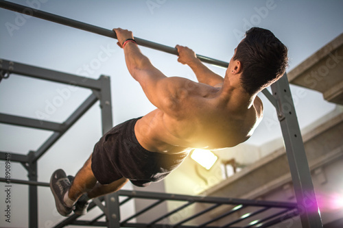 Tela Back view of handsome shirtless man exercising on horizontal bar outdoors